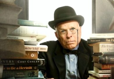 Jim Moore stares into the camera wearing spectacles and a black hat, surrounded by books