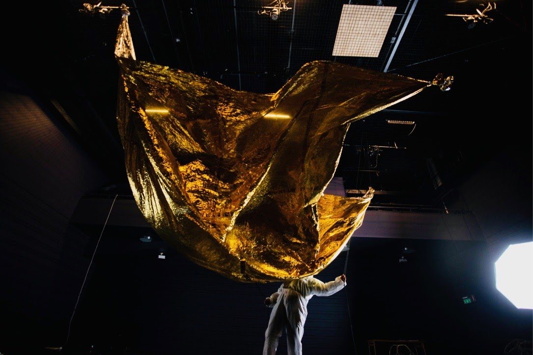 Gold foil unfolds from the ceiling, above an artist wrapped in white