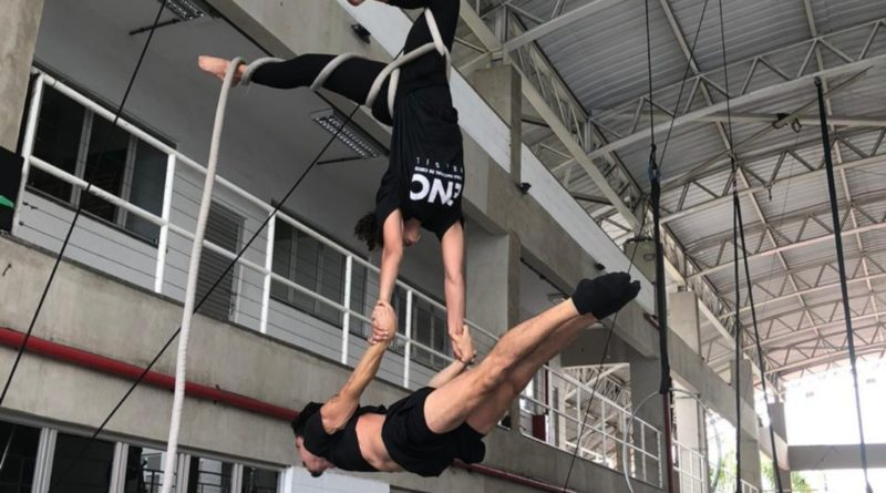 An aerialist hangs from a web holding a flyer in a lever