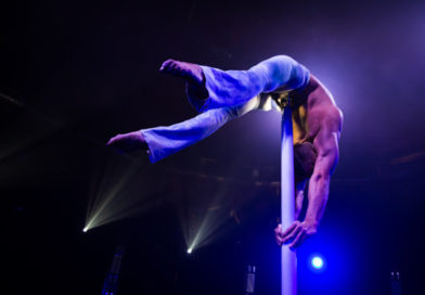 Dima Shine performs a deep back bend while hand balancing