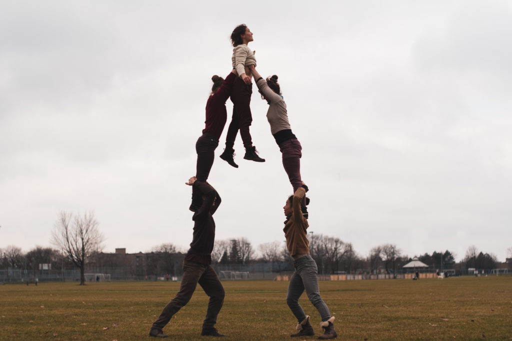 Four circus artists hold two two-highs, holding a fifth artist in between them on top