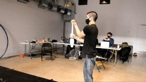Man wearing a mask juggles clubs while man at a table is surrounded by computer equipment