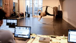 Man on Cyr Wheel and computer equipment in the foreground