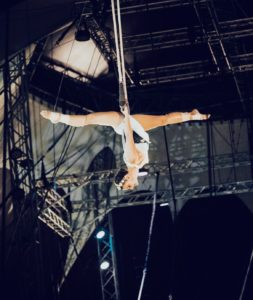 Lydia Nord doing a split on swinging trapeze