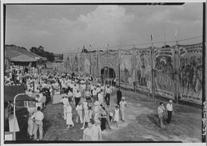 A black and white photo of a circus crowd surrounding a side show tent