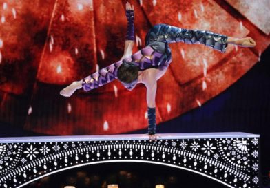 A contortionist performs a one handed handstand on stage