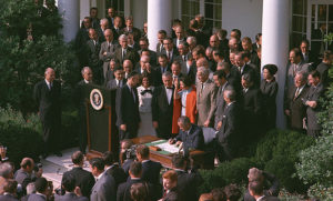 President Lyndon B. Johnson surrounded by officials as he signs a law