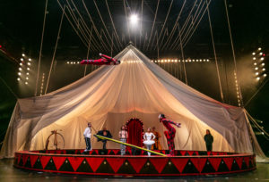 two circus performers in red costumes perform teeterboard in a red circus ring with a white tent in the background