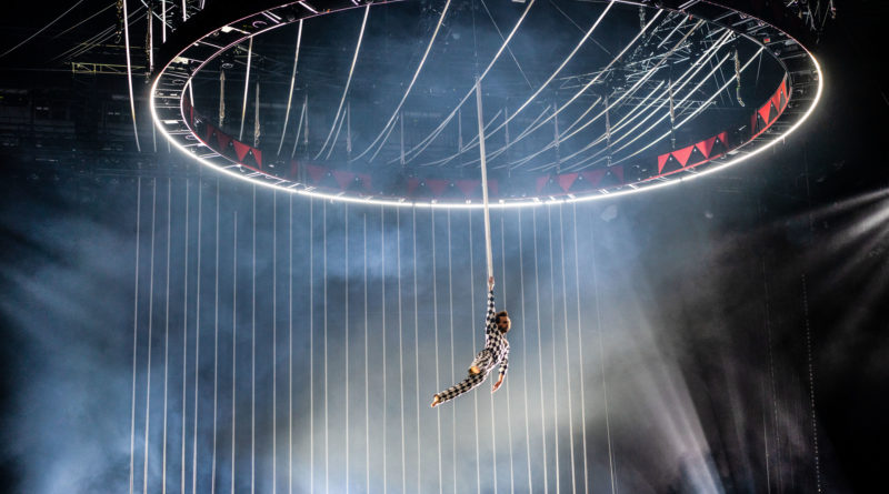 an aerialist flies beneath circular scaffolding with a back drop of ropes