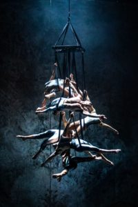 A group of performers hang from an apparatus