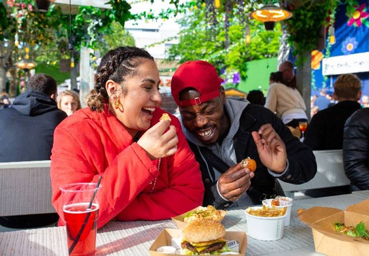 Two patrons laugh together at a table while they enjoy food