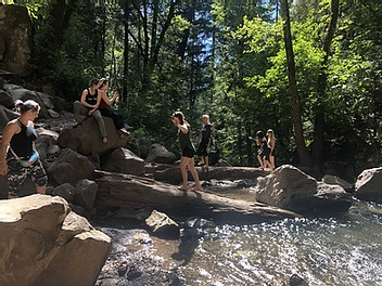 A group of people hikes through a creek