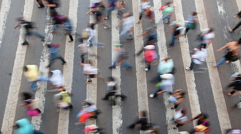 An aerial shot of a crowd of people walking through a street
