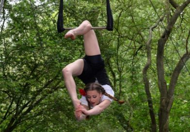 Aerialist pulls her leg over her head hanging from a static trapeze