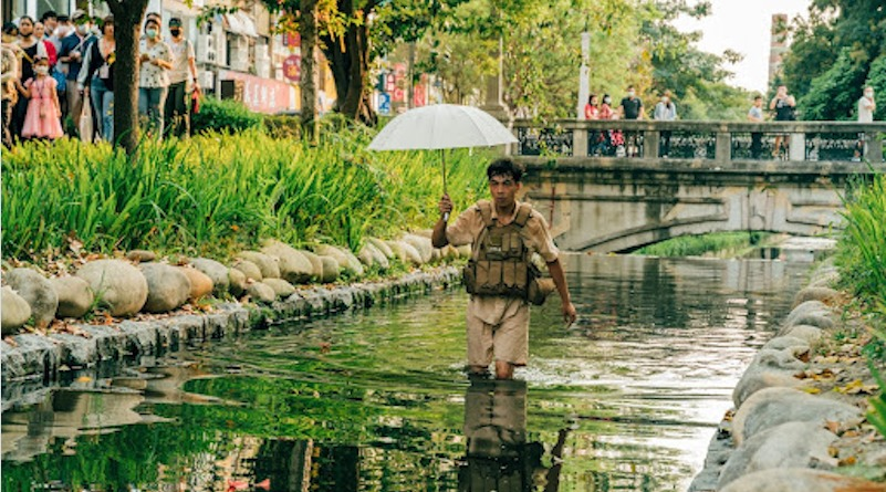 A man wades in a body of water, holding an umbrella