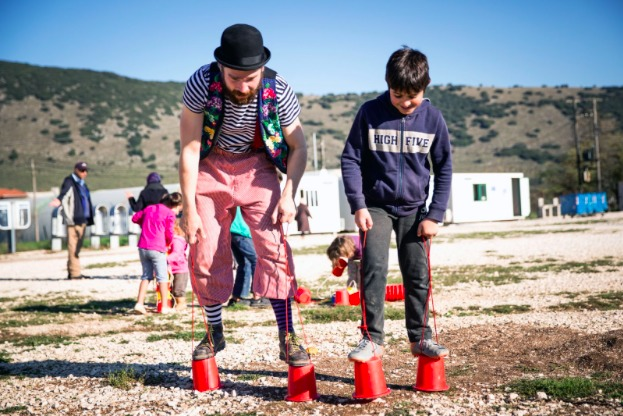 A child and an instructor play with red circus platform shoes
