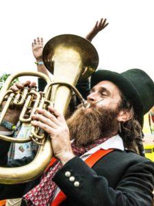 A man with a beard and a top hat joyfully plays the tuba