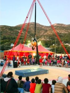 A silks performer hangs from a black silk attached to an A-frame in front of a crowd