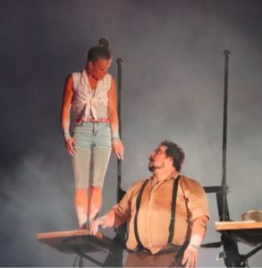 Two performers stand on a Russian cradle platform looking at each other