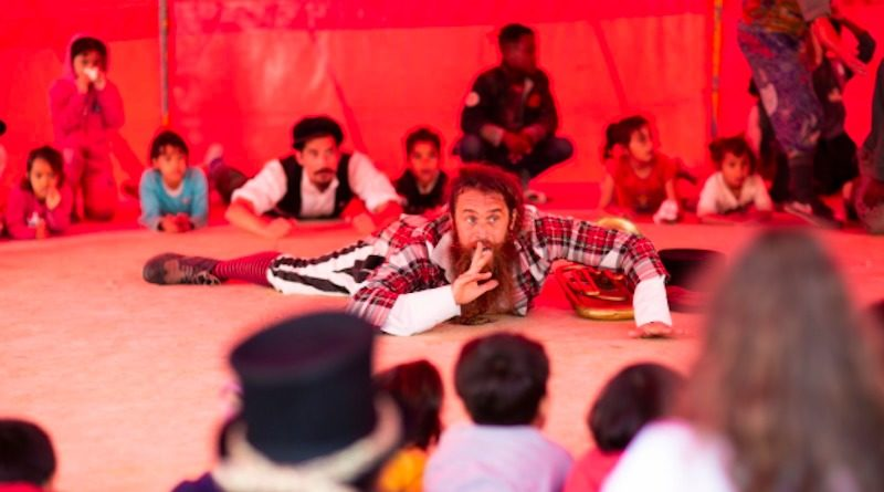 A circus performer lays on the floor, performing a skit for a group of children