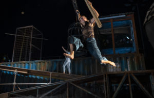 Two acrobats, one hanging above the stage, and one climbing a crate in the background