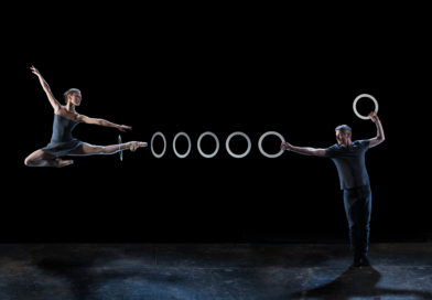 a dancer jumps with a leg extended to the right of the image, a juggling ring is suspended around her ankle a series of juggling rings extend to a circus juggler's hand
