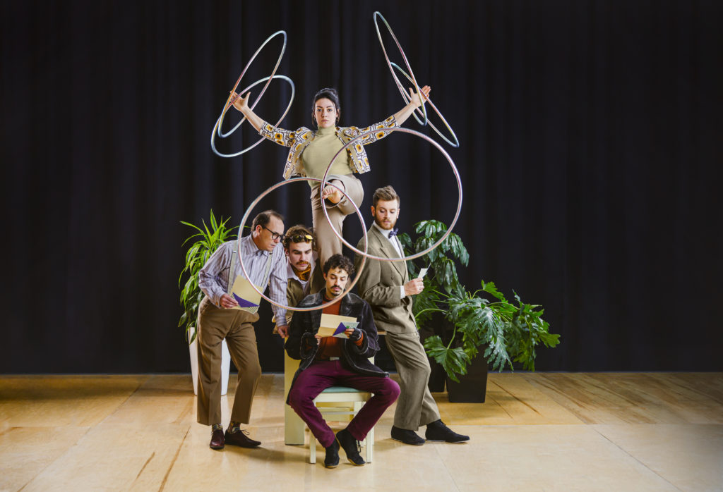 A group of artists face the camera in a pyramid, the top artist is balancing six hula hoops