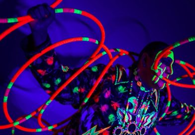A hula hoop artist spins brightly-colored neon hoops under a black light