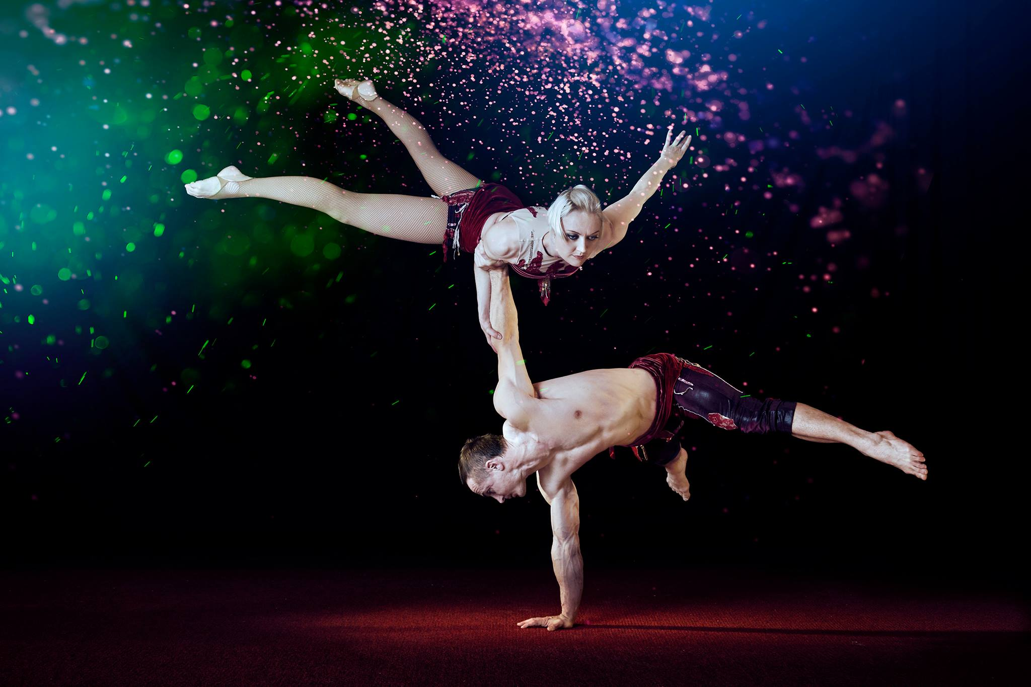 Two hand balancers perform handstands on each other in front of a black background with glitter in the air
