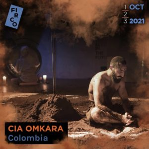 Oskar Mauricio sits in the soil on stage