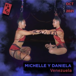 Michelle and Daniela hold each other by the forearm as they hang from their hair in a seated lotus position