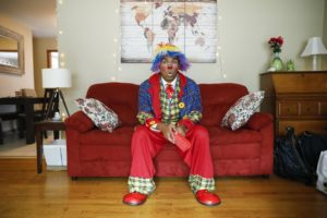 Payaso Coco, seated on his couch, holds an oversized comb