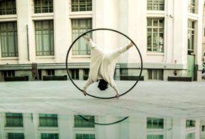 An artist spins upside down on Cyr wheel